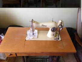 Tikka senovinė siuvimo mašina su dokumentais.
