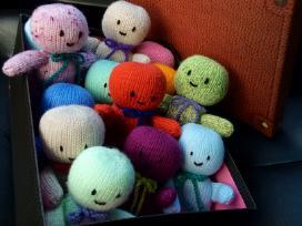 Rankomis megzti žmogeliukai dėžėje